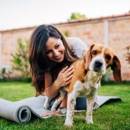 woman outside on yoga mat with dog